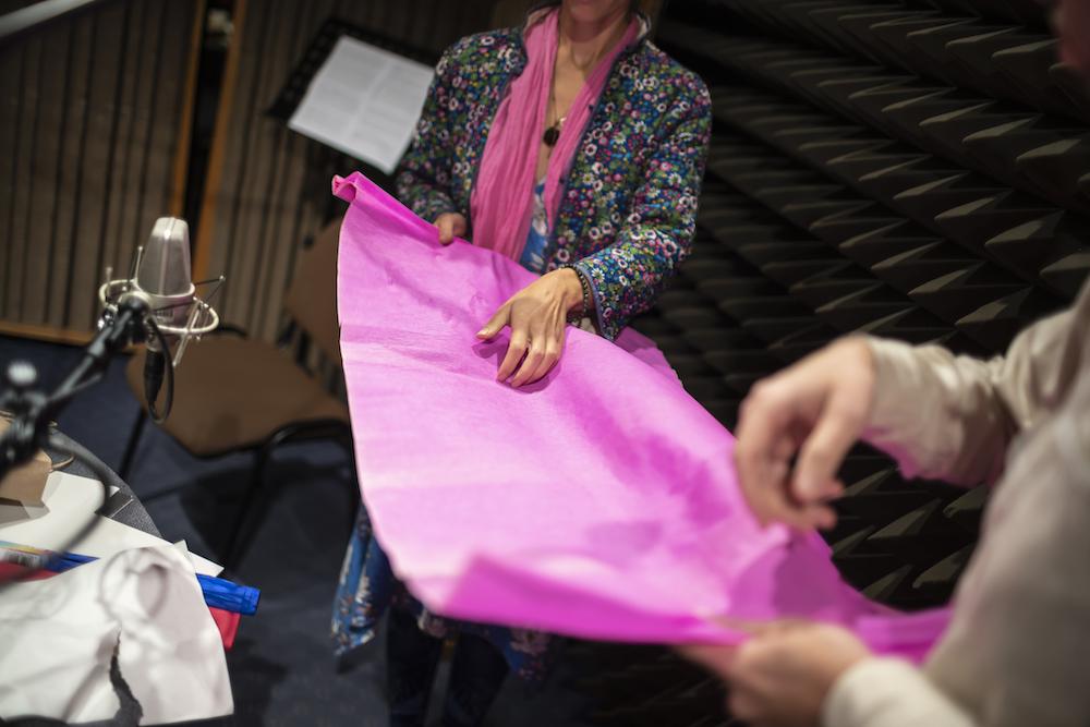 W studio nagrań stoją dwie postaci. Nie widać ich głów, a jedynie korpusy. Trzymają w dłoniach fragment różowej bibuły. Rozciągnięty pomiędzy nimi materiał służy jako instrument, po którym przesuwają palcami. Jego chropowata powierzchnia pozwala wydobyć dźwięki. Jedna z tych postaci ubrana jest w wielokolorowy kaftan. Druga osoba ma na sobie kremową koszulę. Po lewej stronie można dostrzec radiowy mikrofon, który zbiera generowane dźwięki.