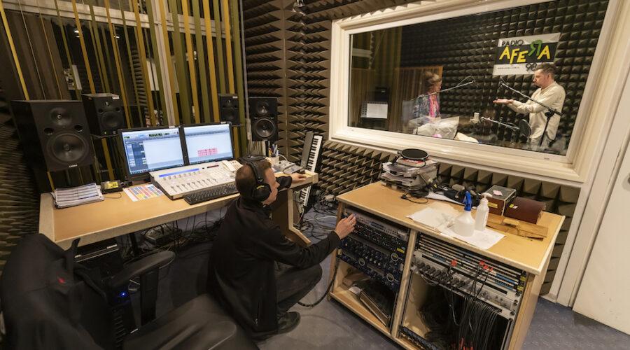 Zdjęcie przedstawia pomieszczenie realizatora nagrania. Pokój wypełniony jest rozmaitym sprzętem radiowym, głośnikami, kabelkami. Na środku, w kucki, siedzi realizator dźwięku. Ubrany jest w ciemne kolory, na uszach ma założone słuchawki. Przesuwa jakieś suwaki. Za szybą w tle widać dwie postaci stojące w studiu nagrań.