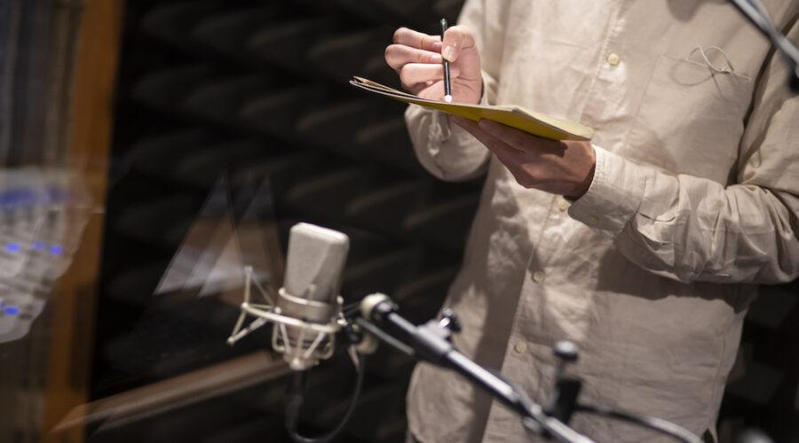 Zdjęcie przedstawia fragment męskiego korpusu. Mężczyzna (nie przedstawiono jego głowy) trzyma w dłoniach tekturę. Służy mu za podstawkę, na której ułożone są nieduże fragmenty papieru, kartki. W prawej dłoni trzyma ołówek, którym kreśli linie na papierze. Ustawione w pobliżu mikrofony rejestrują powstające w ten sposób dźwięki.