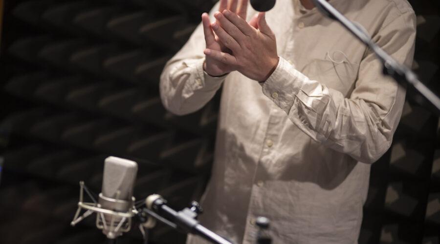 Mężczyzna ubrany w kremową koszulę – uwieczniony tylko od pasa do szyi – stoi wyprostowany. Ma wyciągnięte przed sobą dłonie. Ociera jedna o drugą. Delikatne dźwięki wydobywane w ten sposób rejestruje ustawiony w pobliżu mikrofon.