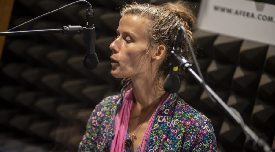 Młoda kobieta, uwieczniona od piersi do czubka głowy stoi blisko mikrofonu. Głowę ma lekko odwróconą w swoją prawą stronę. Grymas na twarzy i ułożenie ust wskazują, że kobieta gwiżdże. Skierowana jest ustami w stronę radiowego mikrofonu. Postać ubrana jest w wielokolorową, pstrokatą tkaninę.