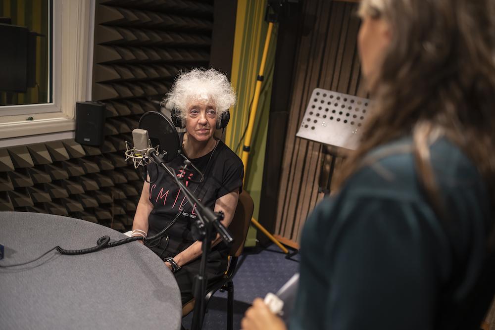 W centralnej części zdjęcia przedstawiono siedzącą przy radiowym stole starszą kobietę. To artystka Izabella Gustowska. Twarz ma promienną, białe, kręcone włosy, delikatny makijaż. Na uszach ma radiowe słuchawki. Blisko ust widać radiowy mikrofon. Jej głowa jest lekko uniesiona – spogląda w stronę innej kobiety, która stoi odwrócona do nas plecami.
