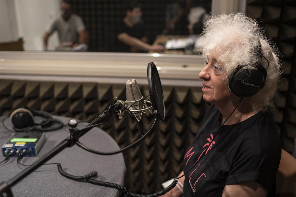 Izabella Gustowska – artystka w dojrzałym wieku – uwieczniona została na tym zdjęciu z lewego profilu. Kobieta ma na uszach czarne słuchawki. Mówi do radiowego mikrofonu. Charakterystyczna dla postaci artystki jest burza białych, kręconych włosów. Kobieta ubrana jest w czarny t-shirt.