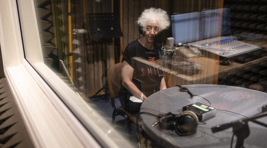 Przedstawiona na fotografii osoba to artystka Izabella Gustowska. Patrzymy na nią zza szyby w radiowym studiu nagrań. Pani Izabella spogląda w stronę realizatora dźwięku. Blisko jej ust znajduje się mikrofon.