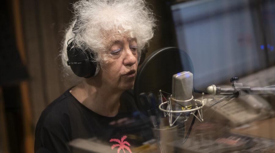 Twarz starszej kobiety. Osoba ujęta jest w trakcie wypowiadania jakichś słów do mikrofonu. To Pani Izabella Gustowska – artystka. Ubrana jest w czarny t-shirt z różowym nadrukiem w kształcie palmy. Na głowie ma burzę białych, kręconych włosów. Na twarzy delikatny makijaż.