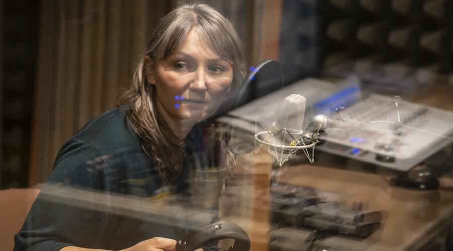 Kobieta w średnim wieku, ubrana w zieloną koszulę, spogląda przez szybę w stronę realizatora dźwięku. Jagna Domżalska – kuratorka wystawy prac Doroty Nieznalskiej – trzyma w dłoniach radiowe słuchawki. Jest lekko pochylona w stronę mikrofonu.