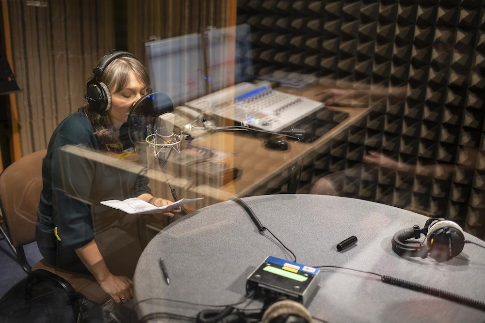 Na fotografii przedstawiono kobietę w średnim wieku siedzącą przy radiowym stoliku. Widzimy ją zza szyby. Trwa nagranie. Jagna Domżalska pochyla się w stronę mikrofonu. W lewej dłoni trzyma kartkę, z której odczytuje tekst. W szybie odbija się pokój realizatora dźwięku.