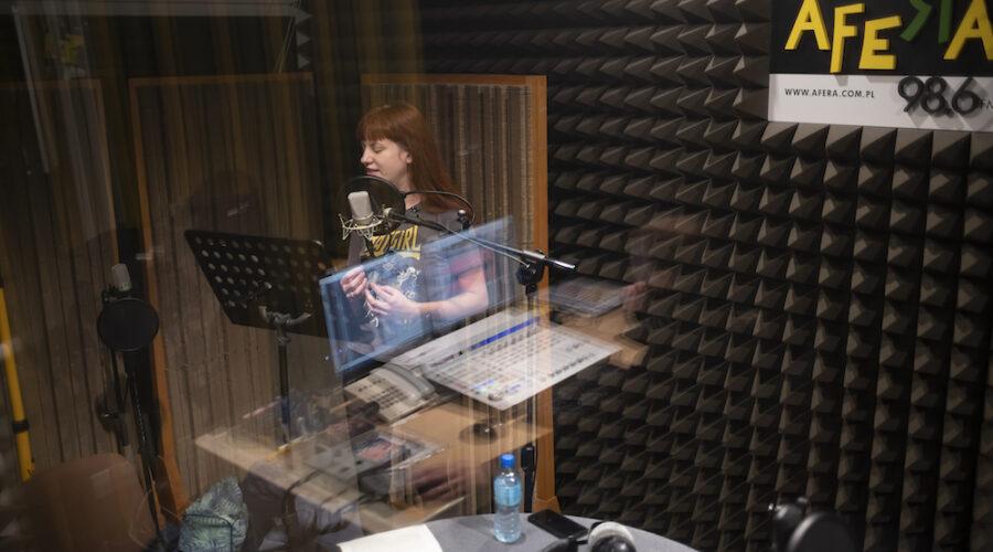 Na zdjęciu przedstawiono studio nagrań. Za szybą stoi rudowłosa dziewczyna ubrana w koszulkę z krótkim rękawem. W skupieniu odczytuje tekst z kartki. Gestykuluje przy tym dłońmi. W szybie odbija się pokój realizatorski oraz zgromadzony w nim sprzęt nagraniowy.