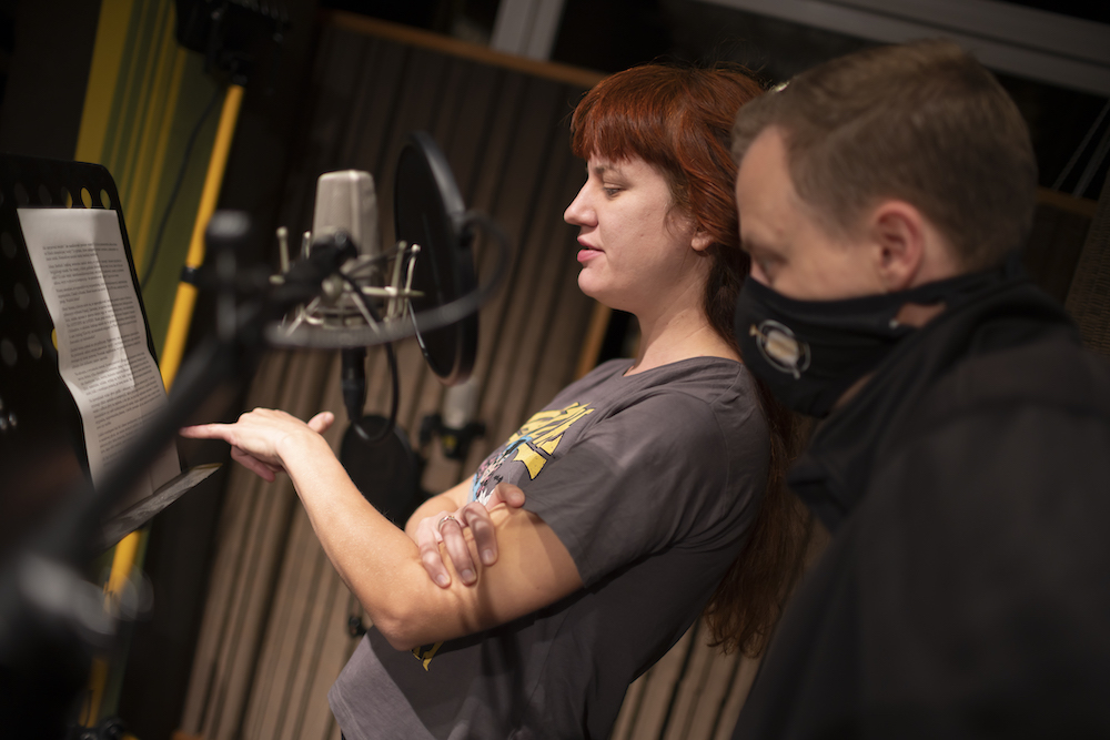 Zdjęcie przedstawia dwóch młodych ludzi konsultujących tekst w studiu nagraniowym. Kobieta ma długie, rude włosy i ubrana jest w koszulkę z nadrukiem. Mężczyzna, ubrany w maskę, podąża za palcem koleżanki, która wskazuje fragmenty tekstu.