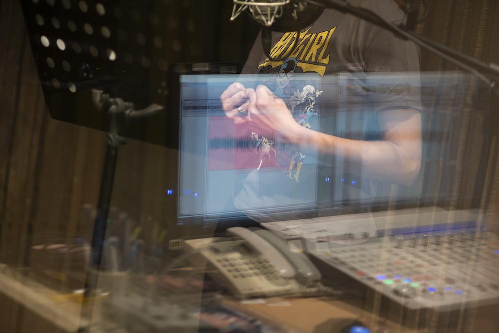 Zdjęcie przedstawia kobietę stojącą za szybą w studiu nagraniowym. Ukazana jest tylko część jej ciała. Ma zaciśnięte pięści – element gestykulacji. W szybie odbija się ekran monitora oraz sprzęt studyjny.
