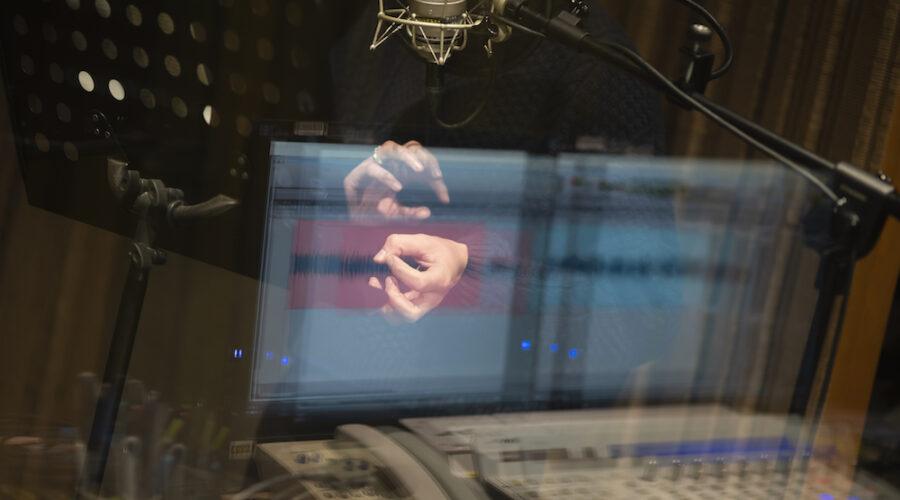 Zdjęcie przedstawia kobietę stojącą za szybą w studiu nagraniowym. Ukazany jest tylko jej ciepły, granatowy sweter oraz dłonie. Osoba wykonuje dynamiczne ruchy, jakby chciała nałożyć jedną dłoń na drugą. Wyraża w ten sposób emocje podczas nagrania. W szybie odbija się ekran monitora oraz sprzęt studyjny.