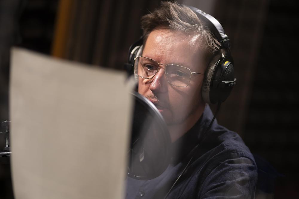 Zdjęcie przedstawia głowę oraz ramiona mężczyzny, w średnim wieku, w okularach, zapatrzonego w kartkę papieru. To Bartek Lis – jedna z osób prowadzących warsztaty. Słuchawki na jego uszach oraz mikrofon w sali wskazują na realizowanie nagrania dźwiękowego.
