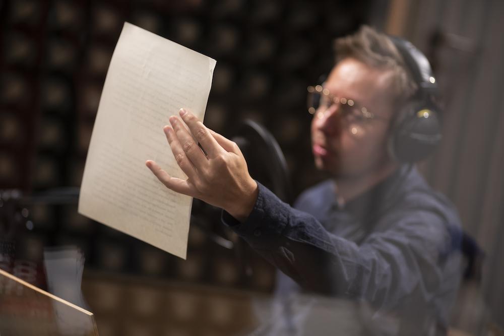 Na pierwszy plan wysuwają się dłonie mężczyzny trzymającego białą kartkę. Postać jest rozmyta, widać jednak granatową koszulę oraz okulary, połyskujące w światłe lampy. Słuchawki na uszach oraz mikrofon w sali wskazują na realizowanie nagrania dźwiękowego.