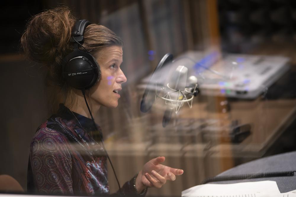 Zdjęcie przedstawia młodą kobietę, w słuchawkach na uszach, mówiącą w stronę mikrofonu. Siedzi ona w studiu nagraniowym, za szybą. Jej włosy ułożone są pękaty kok, który niejako wydłuża smukłą linię tułowia. Jej kolorowa bluzka jest w odcieniach fioletu i błękitu.