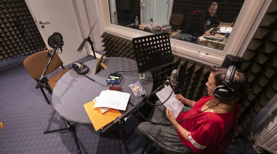 Kobieta siedzi przy okrągłym stole w studiu nagraniowym. Ma krótkie, kasztanowe włosy, intensywnie czerwoną bluzkę i spódnicę w czarną kratę. W skupieniu czyta tekst. Nieopodal jej twarzy czeka już mikrofon – za chwilę rozpocznie się nagranie. Mężczyzna w pomieszczeniu obok czuwa nad przebiegiem sytuacji.