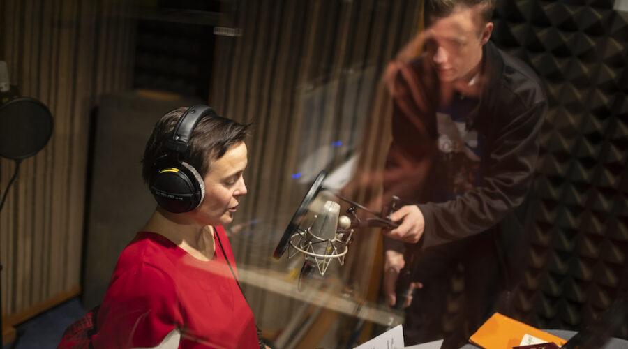Kobieta o kasztanowych włosach i czerwonej bluzce odczytuje tekst. Młody mężczyzna, w czarnej bluzie i koszulce z nadrukiem, asystuje jej, ustawiając odpowiednio mikrofon. Zdjęcie wykonane jest zza szyby. Można wnioskować, że scena odbywa się w studiu nagraniowym.