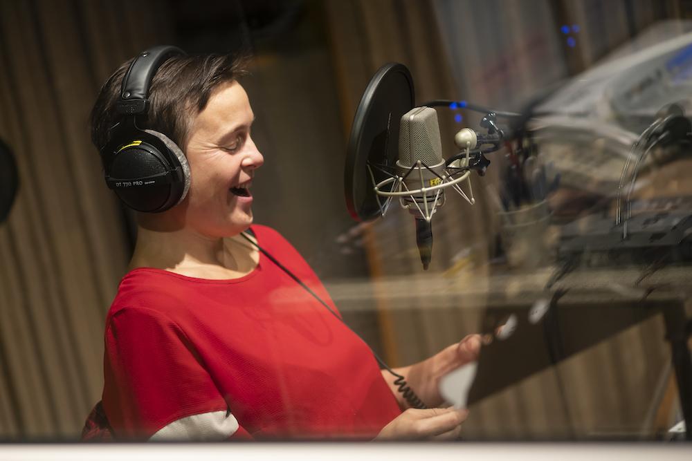 Kobieta w krótkich kasztanowych włosach i czerwonej bluzie uśmiecha się, czytając tekst z kartki. Jej oczy są przymknięte. Przedstawiona jest zza szyby, w studiu nagraniowym. Profesjonalny mikrofon i słuchawki na uszach przypominają o realizowanym nagraniu.