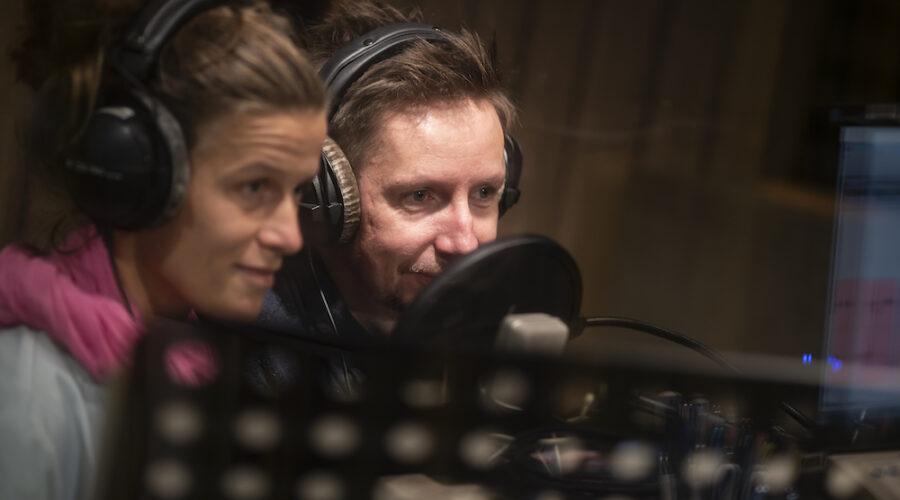 Zdjęcie przedstawia dwie postacie – osoby nagrywające warsztaty. Siedzą blisko siebie, a ich oczy życzliwe spoglądają w tym samym kierunku. Na ich twarzach maluje się zmęczenie, ale również delikatny uśmiech. Uwagę przyciąga zwinięty, różowy szal na twarzy młodej kobiety.