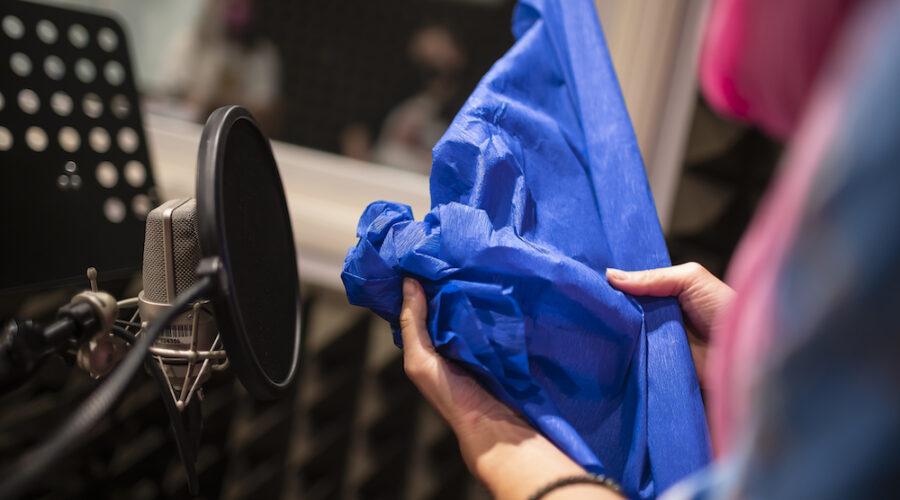 Fotografia przedstawia ludzkie dłonie trzymające niebieską bibułę (krepę). Osoba przystawia materiał do radiowego mikrofonu. Wykonuje różne gesty – marszczy i zgina papier. Powstające dźwięki są rejestrowane.