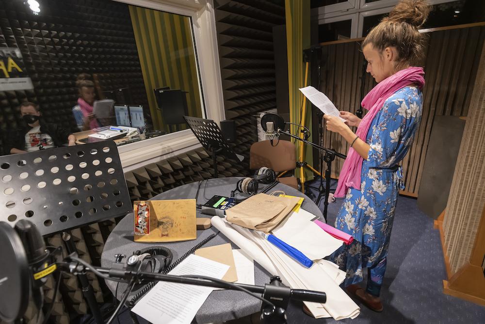 Fotografia przedstawia wnętrze radiowego studia nagrań. W centralnym miejscu stoi okrągły stół, na którym rozłożone są różnorodne, papierowe materiały: fragmenty kolorowej bibuły, kartki papieru o różnej wielkości i fakturze. Nieco po prawej stronie stoi wyprostowana postać kobieca. Ujęta został w pół-profilu. Trzyma przed sobą kartkę papieru. Wygląda jakby odczytywała tekst do jednego z mikrofonów. Stojąca postać to kobieta. Jest ubrana w błękitny kostium z białymi kwiatami, przypominający trochę japońskie kimono. Na szyi ma różową chustę. Włosy blond.