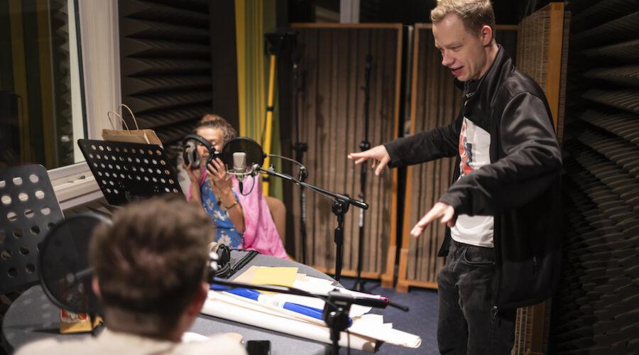 Na zdjęciu przedstawiono trzy osoby. Dwie z nich siedzą przy okrągłym stole w radiowym studiu nagrań. Przygotowują się do nagrania. Zakładają na uszy słuchawki, słuchają ostatnich wskazówek realizatora dźwięku. To właśnie trzecia osoba na tym zdjęciu – młody, rudowłosy mężczyzna ubrany w czarną bluzę. Stoi obok stołu. Ma lekko uchylone usta – przekazuje zapewne jakieś informacje. Rękoma pokazuje jakiś dodatkowy gest.