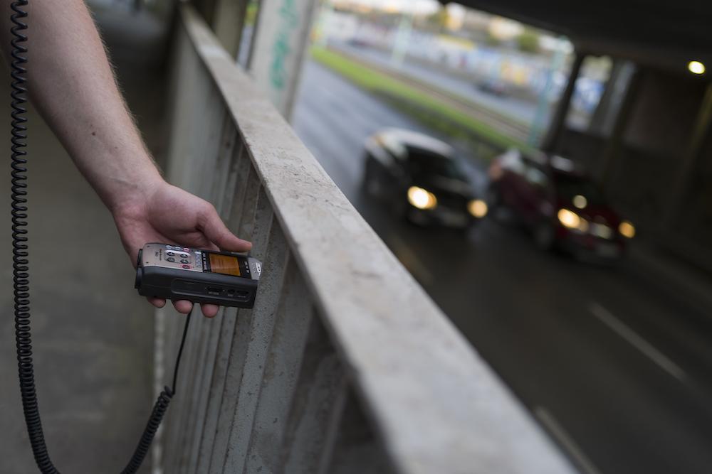 Po lewej stronie fotografii przedstawiono rękę trzymającą dyktafon. Spiralny kabel prawdopodobnie prowadzi do słuchawek, które realizator zapewne ma założone na uszach. Po prawej stronie zdjęcia można dostrzec przejeżdżające pod wiaduktem dwa samochody. Auta mają zapalone światła.