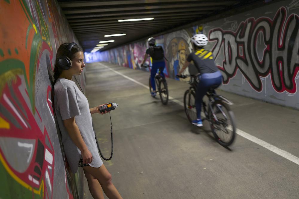 Na fotografii przedstawiono z profilu młodą dziewczynę ubraną w beżową sukienkę, która opiera się o jedną ze ścian w podziemnym tunelu. Osoba ma na uszach słuchawki, a w lewej dłoni trzyma dyktafon. W wąskim tunelu przejeżdżają rowerzyści. Z pewnością dziewczyna rejestruje dźwięki wydawane przez jednoślady. Ściany tunelu pomalowane są w różnobarwne graffiti.