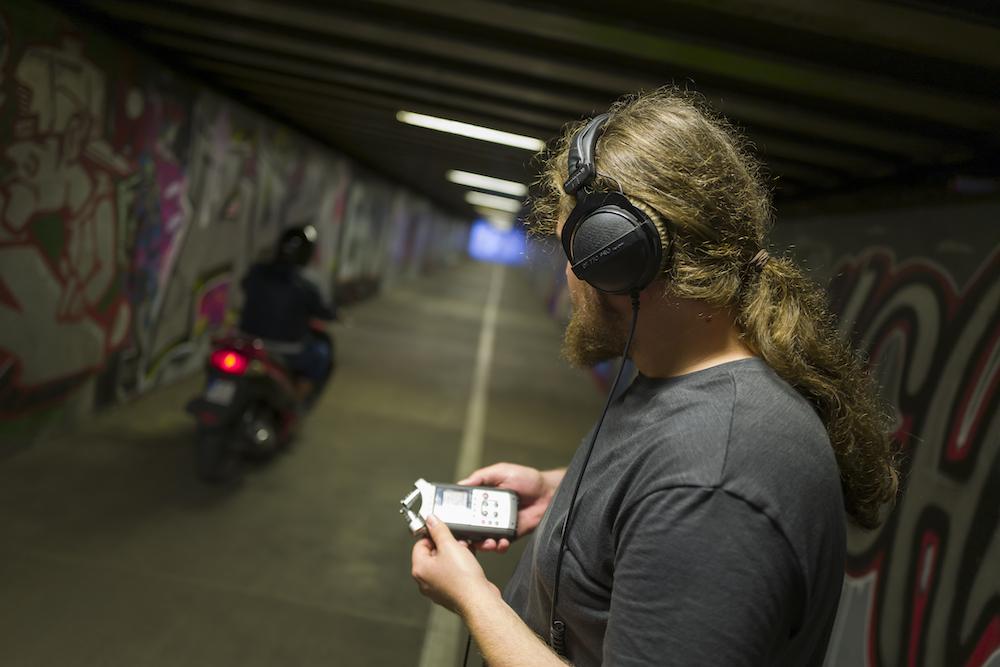 Zdjęcie przedstawia popiersie młodego mężczyzny odwróconego do nas plecami. Chłopak stoi w tunelu. Na uszach ma założone słuchawki, a w dłoniach trzyma dyktafon. Jego głowa skierowana jest w stronę przejeżdżającego właśnie motocykla. Ściany tunelu pomalowane są w różnobarwne graffiti.