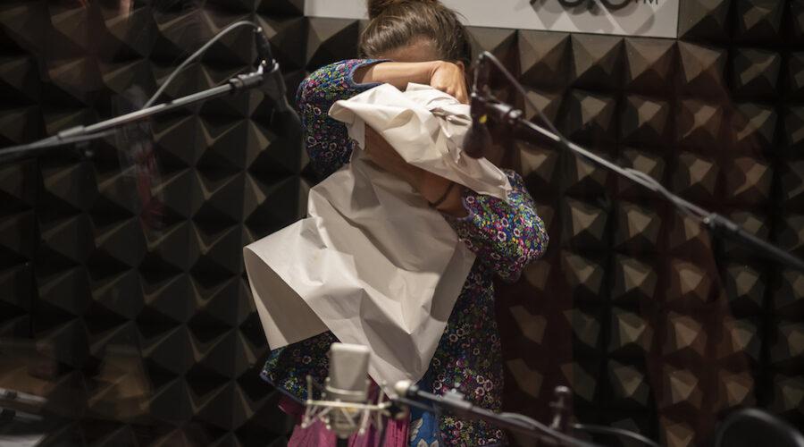W radiowym studiu stoi wyprostowana kobieta. W rękach trzyma duży fragment szarego papieru. Ugniata go i formuje z niego bryłę. Nie widać jej twarzy, jedynie czubek głowy – czoło i spięty pukiel włosów. Na pierwszym planie stoją radiowe mikrofony, zbierające dźwięki generowane przez ugniatanie papieru.