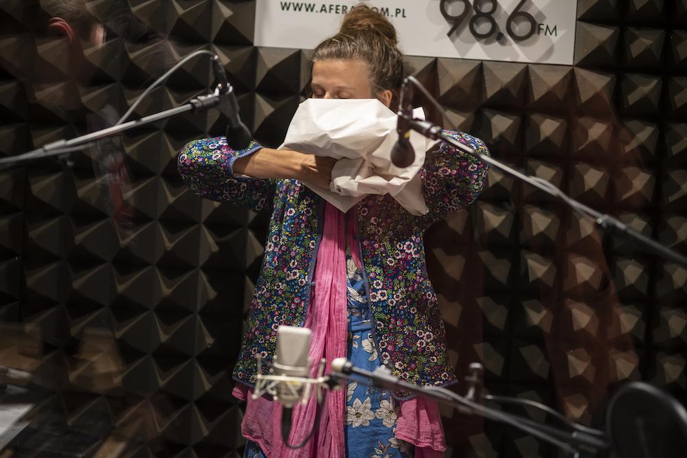 W radiowym studiu stoi wyprostowana kobieta. W rękach trzyma fragment szarego papieru. Ugniata go i formuje z niego bryłę, którą przysłania swoją twarz. Widać tylko czubek jej głowy – czoło i spięty pukiel włosów. Na pierwszym planie stoją radiowe mikrofony, zbierające dźwięki generowane przez ugniatanie papieru. Kobieta ubrana jest w wielowarstwową, wielokolorową kreację.