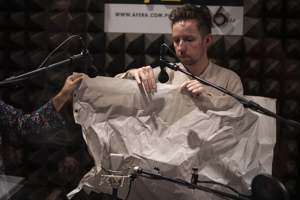 Na zdjęciu przedstawiono krótko ostrzyżonego mężczyznę w średnim wieku. Ubrany jest w kremową koszulę. Przed sobą trzyma duży fragment szarego papieru. Papier jest pogięty i pomarszczony. Mężczyzna prowadzi swoją prawą dłoń po jego górnej krawędzi. Wydobywa w ten sposób specyficzny dźwięk. Twarz ma skupioną, głowę opuszczoną lekko w dół. Na pierwszym planie stoją wyciągnięte radiowe mikrofony, zbierające powstające dźwięki.